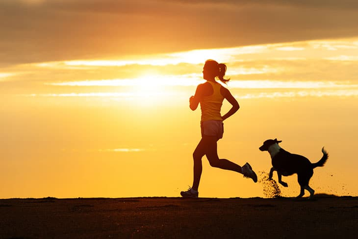 Woman running and a dog chasing her
